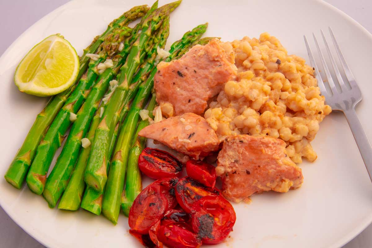 prepared meal using salmon bowl, seared asparagus with garlic butter, roasted tomatoes